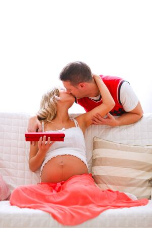 Young pregnant woman kissing her husband who present her jewelery photo