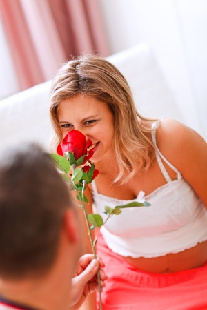 Young pregnant woman smelling flower presented by her husband photo