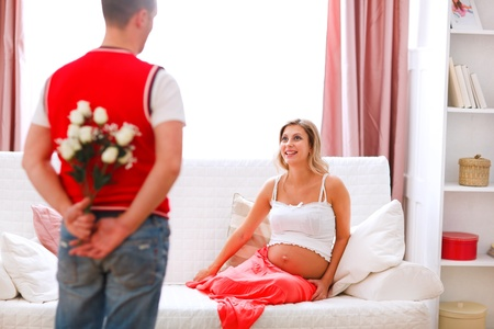 Husband hiding flowers from his excited pregnant wife photo