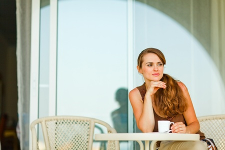 sagacious: Thoughtful woman sitting on terrace and having cup of coffee  Stock Photo