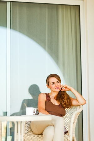 sagacious: Thoughtful pretty woman with cup of coffee sitting on terrace