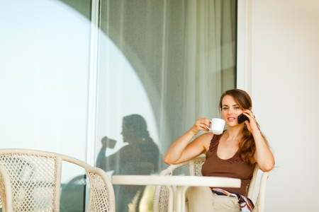 disquieted: Concerned young female sitting on terrace with cup of coffee and speaking mobile