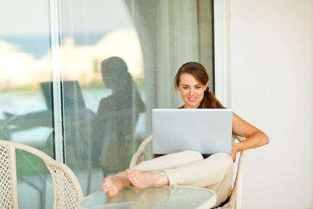laptop outside: Portrait of beautiful woman working on laptop on terrace