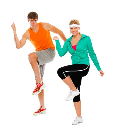 Healthy girl and guy in sportswear doing aerobics isolated on white