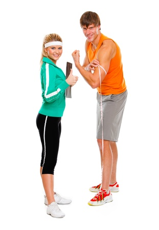 male athlete: Male athlete measuring biceps and smiling girl in sportswear showing thumbs up
