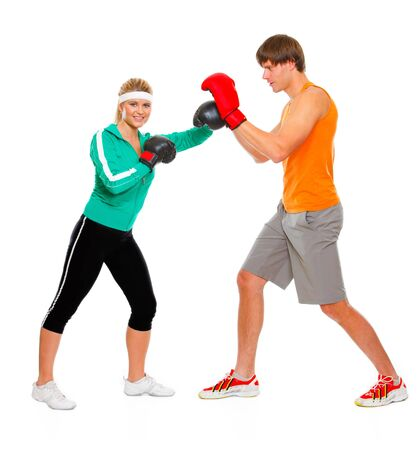 Fitness girl training boxing with help of personal trainer isolated on white  photo