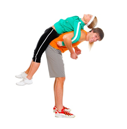 Handsome young man taking slim girl in sportswear on his back isolated on white Stock Photo - 11666191