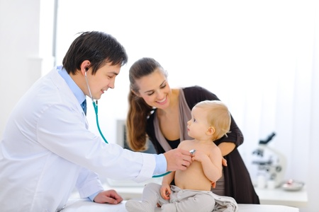 pediatrics: Surprised baby being checked by a doctor using a stethoscope  Stock Photo