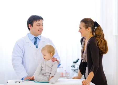 Pediatric doctor talking with mother while baby playing with stethoscope  Stock Photo - 11640689