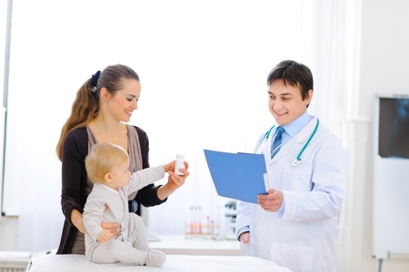 Mother and baby holding bottle of vitamins on examination of pediatric doctor  photo