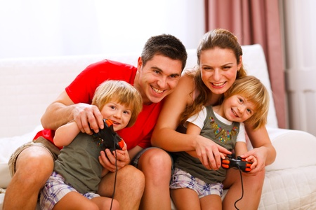 Mom and dad playing with twins daughter on console  photo