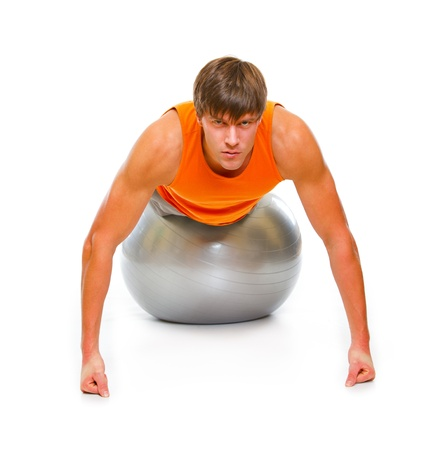 Young man in sportswear making push up exercise on fitness ball isolated on white