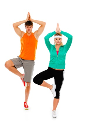 Fitness girl and man in sportswear doing yoga isolated on white