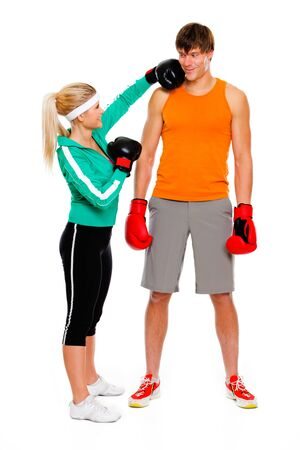Slim girl in boxing gloves punching man isolated on white  photo