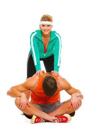 Fitness girl in sportswear helping guy doing stretching exercise on floor  photo