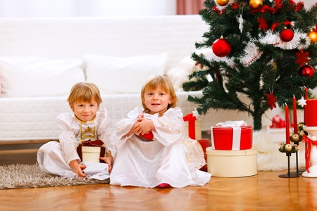 Two happy twins girl sitting with presents under Christmas tree  photo
