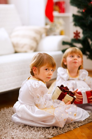 One of twins girl sitting with present with serious expression   photo