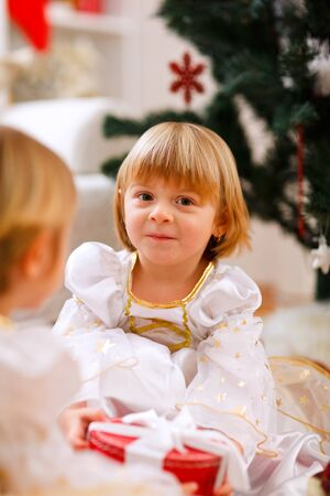 Two happy twins girl sitting with presents near Christmas tree  photo