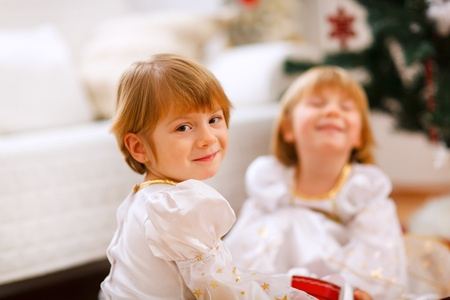 playing on divan: Portrait of happy girl playing with sister near Christmas tree  Stock Photo