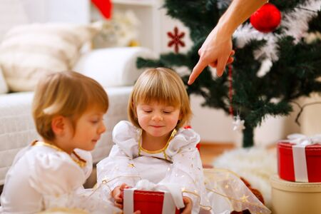 Hand of parent pointing on present to twins girl Stock Photo - 11825749