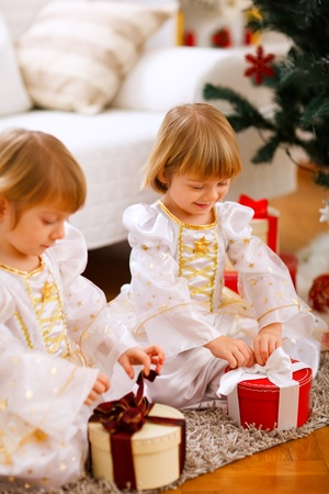 Two happy twins girl opening presents near Christmas tree  photo
