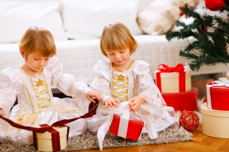 Two happy twins girl opening presents near Christmas tree Stock Photo - 11825791