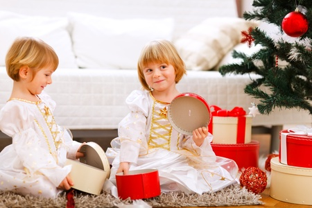 Two smiling twins girl opening presents near Christmas tree