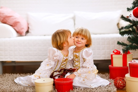 Twin girl kissing her sister near Christmas tree with gifts  photo