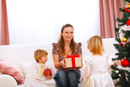 Two twins girl presenting gift to mother near Christmas tree  photo