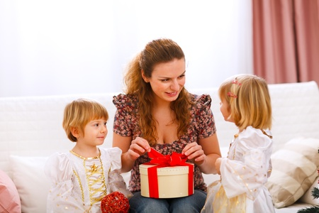 opening gift: Mother opening gift presented by twins girl
