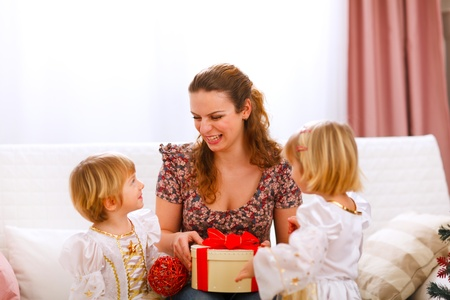 Happy mother holding gift of her twins daughters  photo