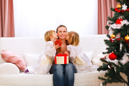 baby near christmas tree: Two twins daughters presenting gift to mother and kissing her near Christmas tree