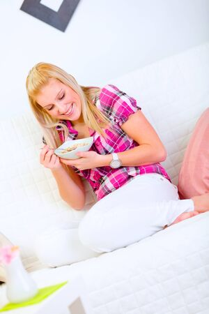 Smiling young woman sitting on sofa and eating muesli photo