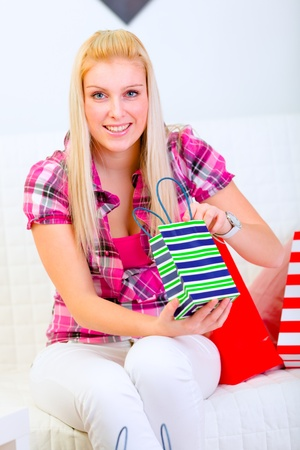 Lovely woman sitting on sofa and holding shopping bags in hands photo