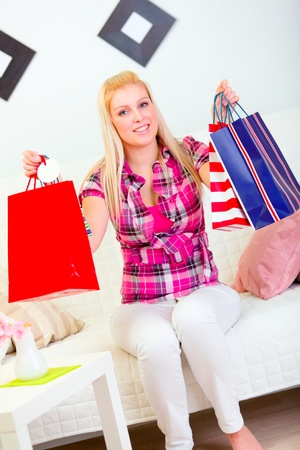 Smiling pretty woman sitting on divan and holding shopping bags in hands photo