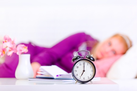 Alarm clock on table and woman laying on sofa in background Stock Photo - 11825836