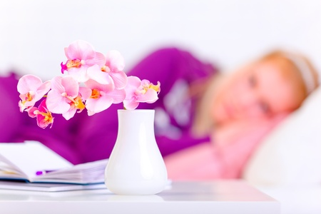Flowers in vase on table and woman laying on sofa in background