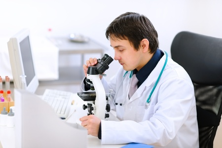 Medical doctor using microscope   photo