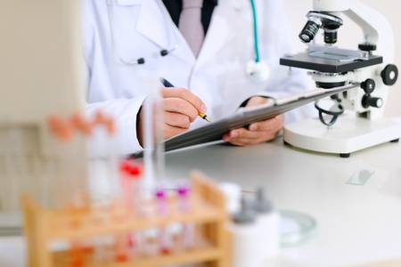 medical clipboard: Medical doctor writing something in clipboard at office table. Close-up.  Stock Photo