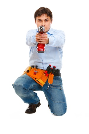 Construction worker using pointing drill as a gun in camera  photo