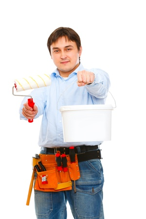 Construction worker stretching paint bucket and brush  photo