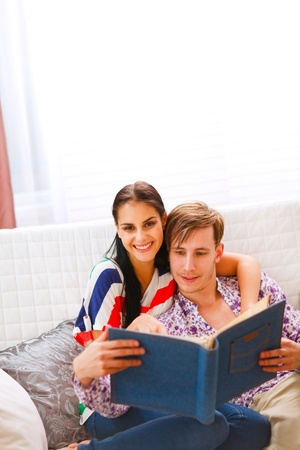 Happy young couple sitting on couch and looking photo album   photo
