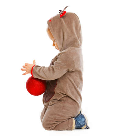 interrogatively: Baby playing with Christmas ball in profile