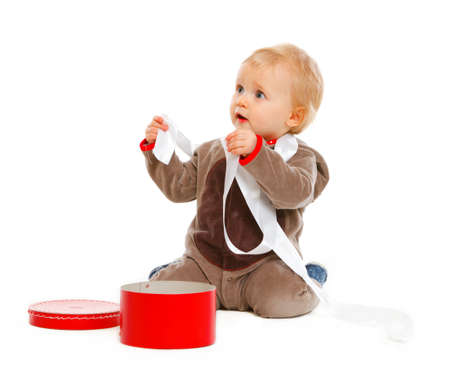 interrogatively: Curious cute baby with open Christmas gift box