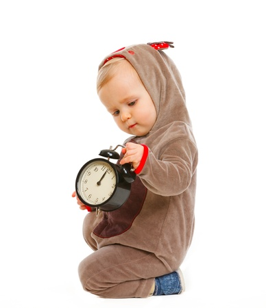 interrogatively: Adorable baby in costume of Santa Clauss reindeer with alarm clock