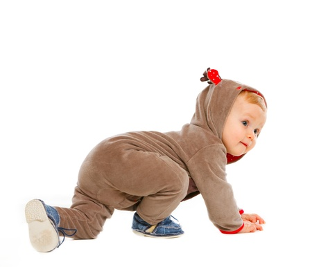 Curious baby in costume of Santa Claus's reindeer crawling  photo
