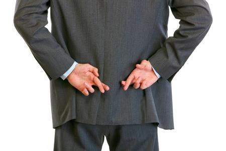 Close-up op handen met gekruiste vingers achter zakenman terug