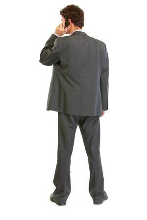 elegant business man: Uomo d'affari in piedi moderno torna alla fotocamera e parlando cellulare