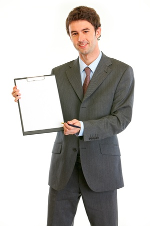 Smiling modern businessman giving clipboard for you to sign  photo