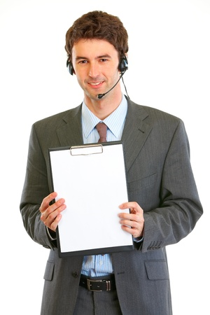 Smiling modern businessman in headset showing blank clipboard  photo